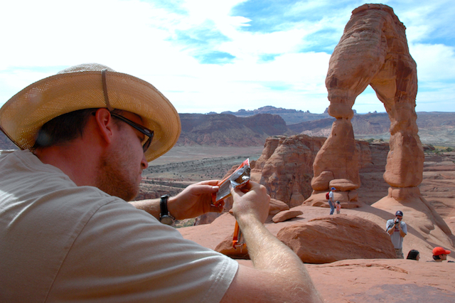 Dave reading a granola bar wrapper at Delicate Arch, September, 2006